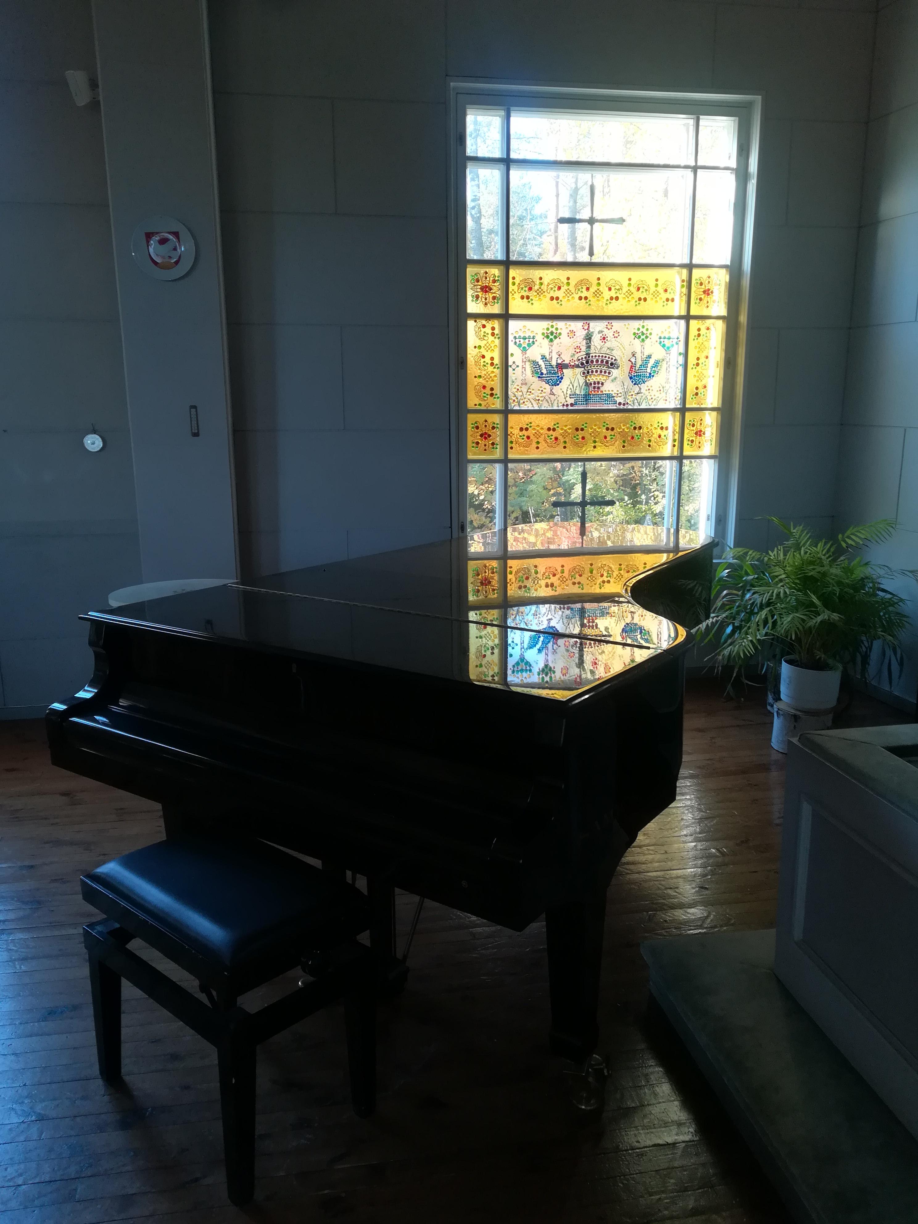 Flyygeli konsertteja varten. Taustalla kaunis lasimaalaus kirkon ikkunassa.